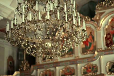 sobor: in the church on the background of the icons large chandelier with candles Stock Photo
