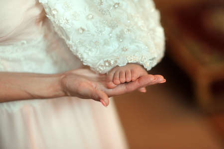 firstborn: gentle mothers hand holding a small baby foot Stock Photo