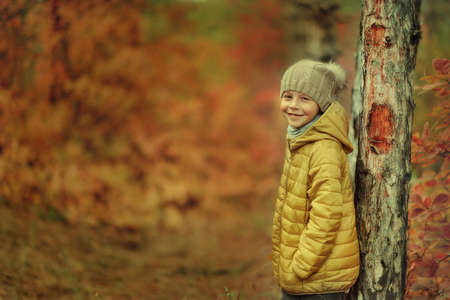 yellow jacket: little boy in a yellow jacket and knit cap stands near a tree in autumn forest