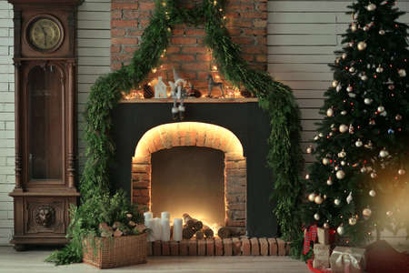 festively: in a room lit festively decorated fireplace with candles and pine needles