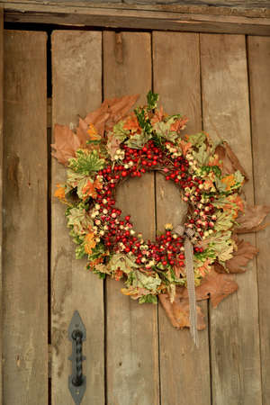 weighs: on a wooden door weighs a wreath of yellow autumn leaves and red berries