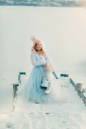 winter vacation: snowy winter wooden bridge near the frozen river is a cute girl in a magnificent dress with skates