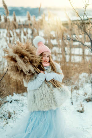 fur coat: cute little girl in a fur coat and hat with a cane snowy winter Stock Photo