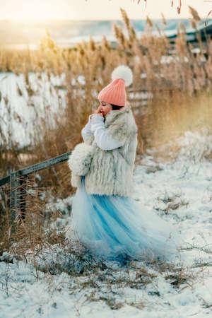 manteau de fourrure: mignonne petite fille dans un manteau de fourrure avec neigeux embrayage hiverne dans les roseaux