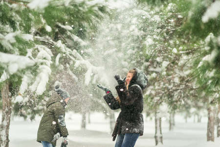 rollick: winter in a park with pine trees, mother and son playing in the snow Stock Photo