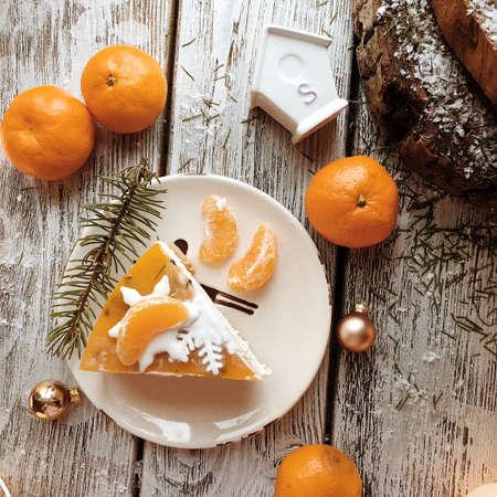 fir twig: on a wooden stand orange dessert with fir twig and mandarins