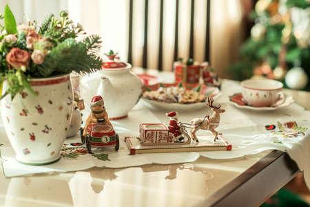 New Year's tea party aan de tafel met een mooie gebruiksvoorwerpen en decoratie Stockfoto