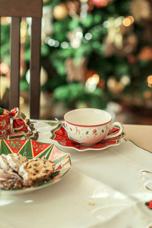 on the table are pretty tea cup and saucer and a plate of dessert