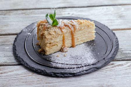 porcion de torta: sobre la mesa un plato negro con un pedazo de la torta napoleon con una ramita de menta y azúcar en polvo Foto de archivo