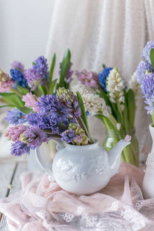 openwork: White teapot with a large bouquet of multicolored hyacinths and a cup on a pink openwork Stock Photo
