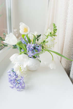 hyacinths: sunny day on the windowsill is a white vase with a bouquet of flowers from tulips and hyacinth Stock Photo