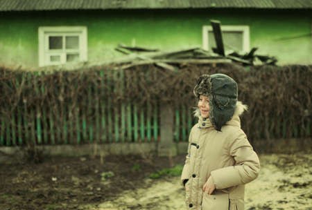 unrecognisable people: in the village at the house with a fence cheerful little boy in a jacket and hat with earflaps Stock Photo