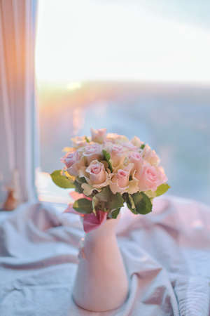 bow window: at sunset at the window in a pink vase bouquet of roses with bow