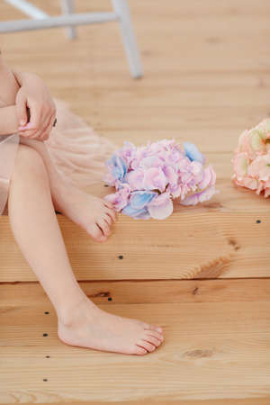 painted toes: on the wooden floor barefoot child and bunch delicate flowers Stock Photo