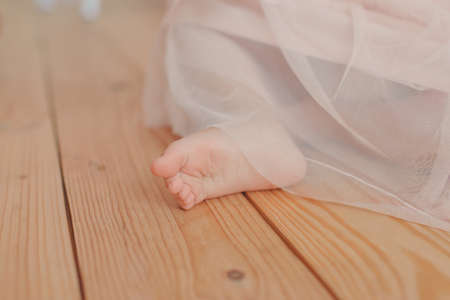 painted toes: on the wooden floor of the childs bare feet in the magnificent pink skirt