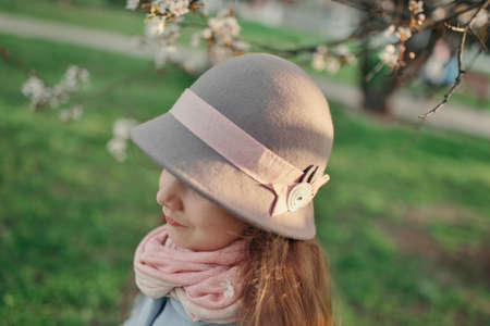 light complexion: in a lush garden in the sunlight girl in gray hat