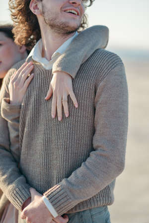 atonement: womans hand tenderly hugging a man in a gray sweater Stock Photo