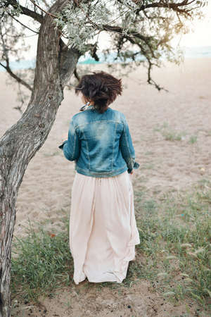 denim jacket: woman in a long dress and a denim jacket from an old tree