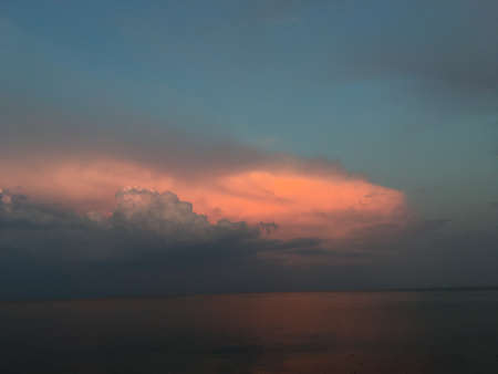 and the magnificent: beautiful sunset over the water with magnificent clouds on the horizon