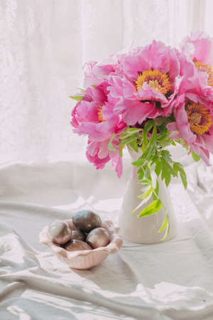 paschal: on the windowsill bunch of decorative pink peonies in a vase and easter eggs Stock Photo