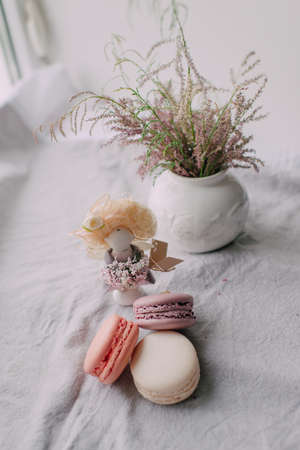 macarrones: window white vase with a bouquet and a wonderful doll with cake Macaroni