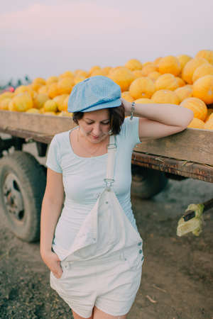 Posing woman in blue cap from carts with ripe yellow melons