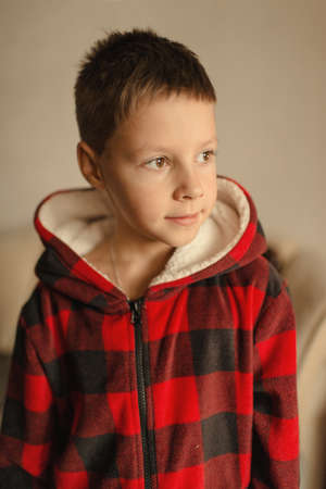 red plaid: portrait of a cute boy in a red plaid jacket with a hood