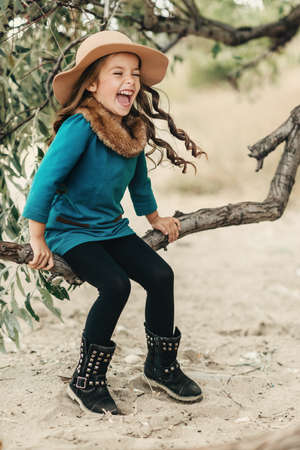 poses in the autumn forest beautiful girl with long hair in a hat and a coat with fur Stock Photo