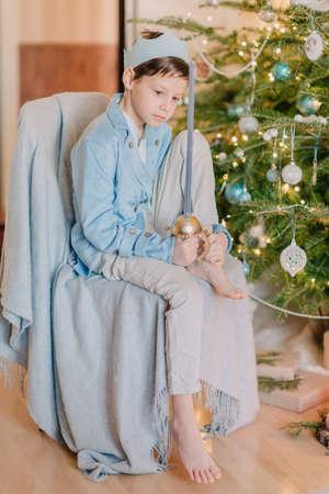 corona navidad: cerca de niño hermoso árbol de Navidad en un príncipe azul vestido con una corona y con una espada Foto de archivo