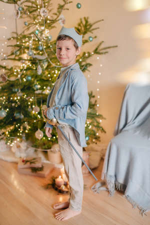 near beautiful Christmas tree little boy in a blue prince dressed in a crown and with a sword