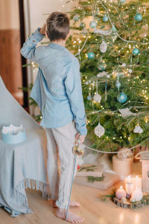 near beautiful Christmas tree little boy in a blue suit and a prince with a sword Stock Photo