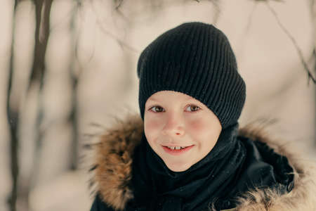 grey eyed: boy in a hat in the snow Stock Photo