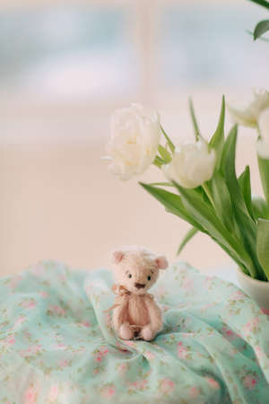 teddy bear and a bouquet of white spring flowers photo