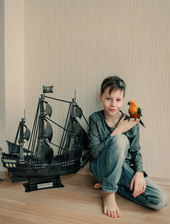 in the room on the floor and black sailboat sits a boy pirate with a parrot in a large photo