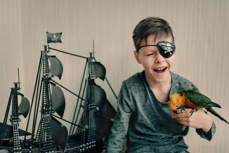 Black sailing ship and pirate boy playing with a large parrot photo