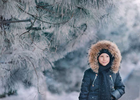 boy in a jacket with a hood with fur walks snow park with trees in the snow Stock Photo
