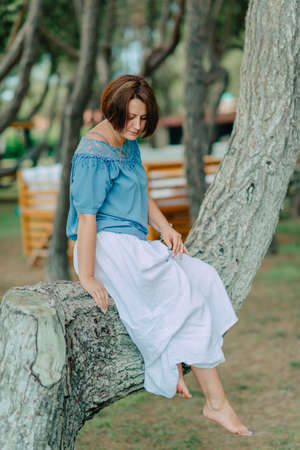 in the park woman in a white skirt and blue blouse barefoot sits on a tree branch Stock Photo