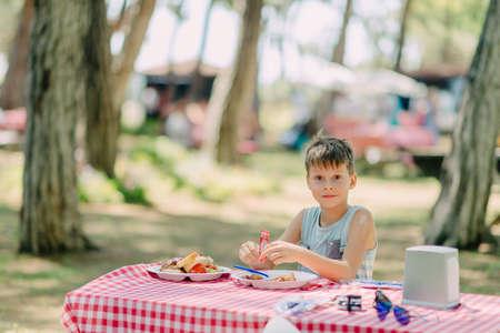 poquito: El muchacho come en un parque de verano