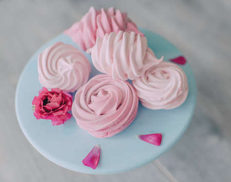 On a wooden table a blue plate with pink meringue pie and a flower
