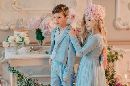 little boy and girl in the blue dress in the Studio with flowers and candle photo
