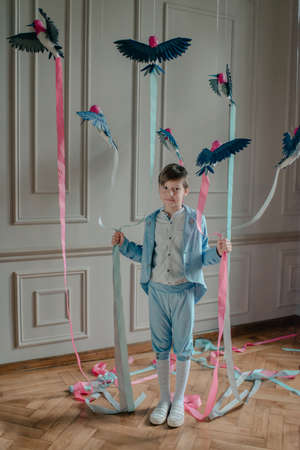 in the Studio the boy in the blue suit with birds and colored ribbons photo