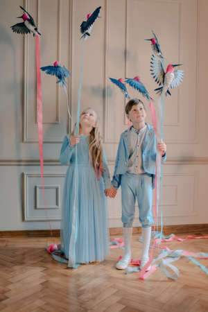 in the Studio the boy in the blue suit and the girl in the blue dress with birds and colored ribbons photo