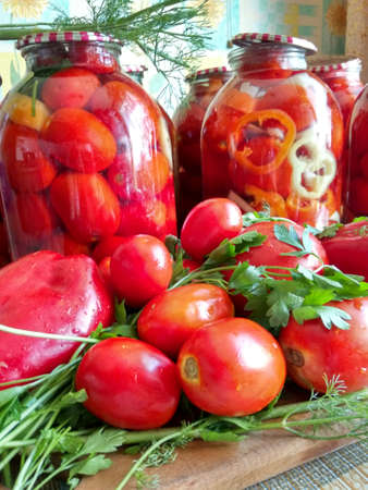 Home canning for the winter glass jars with red tomatoes and greens Stock Photo