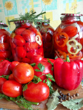 sterilized: Home canning for the winter glass jars with red tomatoes and greens Stock Photo