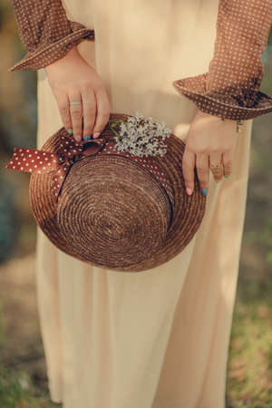 Female hands with a beautiful manicure hold a straw, brown hat