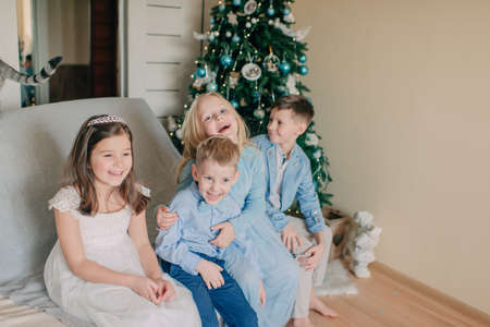 Childrens sits on the sofa at the New Year tree photo