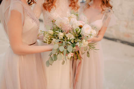 Girls in white dresses with a bouquet of flowers