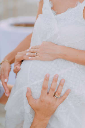 pregnant woman in white dress in her arms of her husband