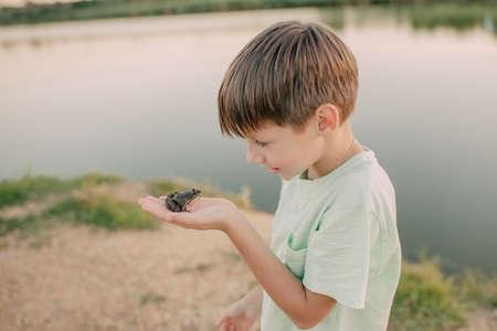 de jongen houdt een pad op de oever van de rivier