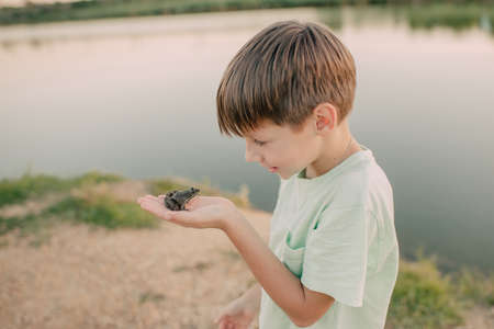 the boy is holding a toad on the river bank